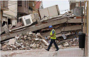Home caminant per un carrer en ruïnes.